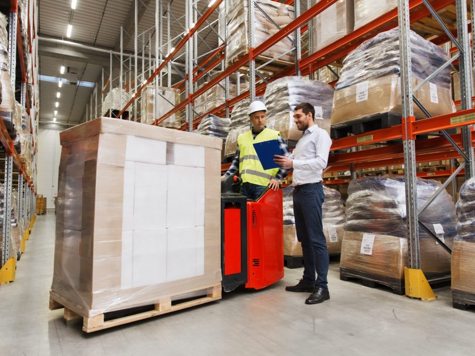 wholesale, logistic, people and export concept - manual worker on forklift loader and businessmen with clipboard at warehouse