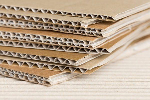 Cardboard pile on corrugated cardboard texture. Industrial background.