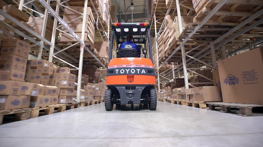 Forklift Trucks Move Between Large Metal Shelves at a Modern Warehouse and Unload Pallets with Cardboard Boxes.