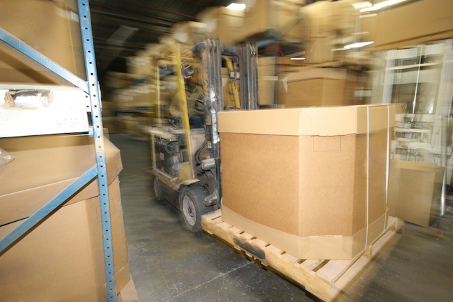 busy lift truck driver moves inventory or box on a skid in a manufacturing plant