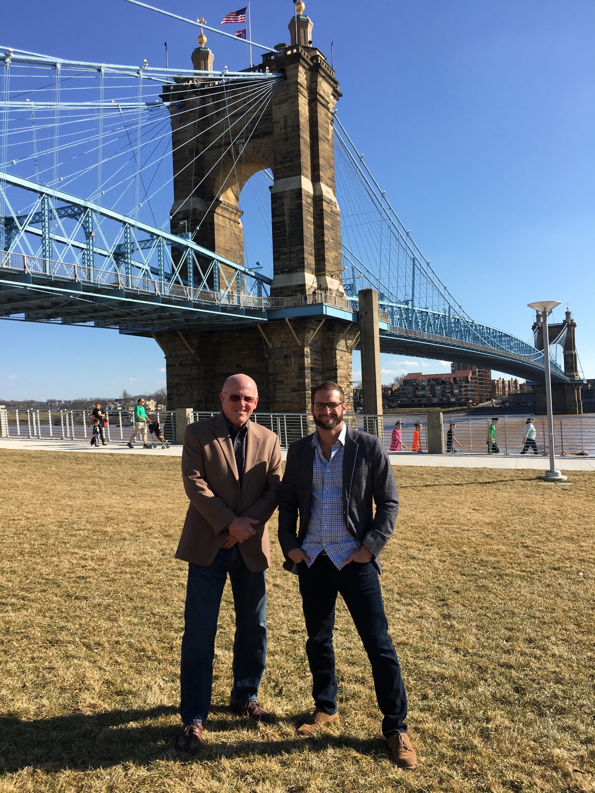 two men standing in front of a bridge and smiling