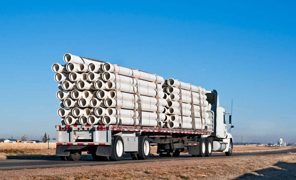 flatbed truck hauling large pipes